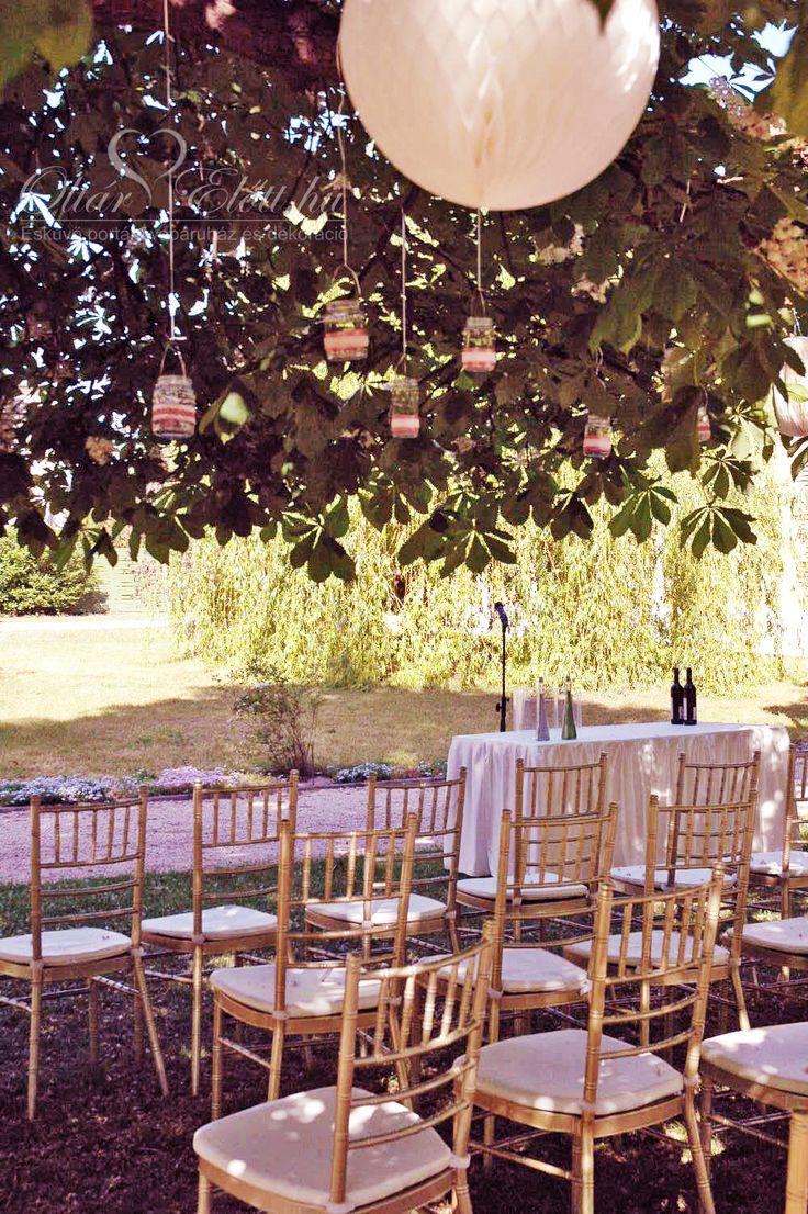 A vendégek chiavari székeken ülhettek, a fejük felett hangulatos befőttes üvegeket lógnak mécsesekkel.