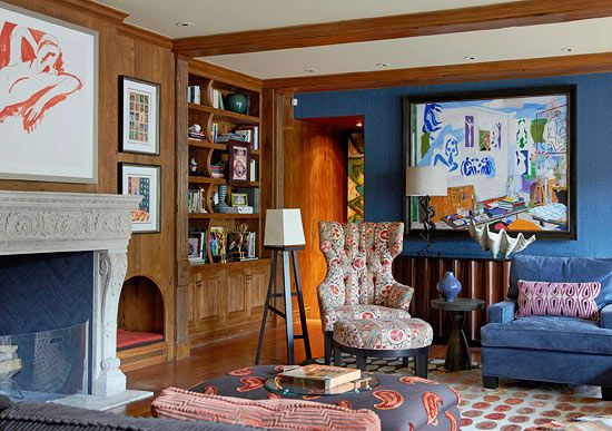 Family Room Patterns mix in the blue family room. A  navy herringbone pattern inside the fireplace brings a modern twist to the  antique French mantel. To the right of the fireplace, a niche in the wall  serves as a cozy dog bed. The blue wall hosts a painting by one of Sela's  favorite artists, Damien Elwes.