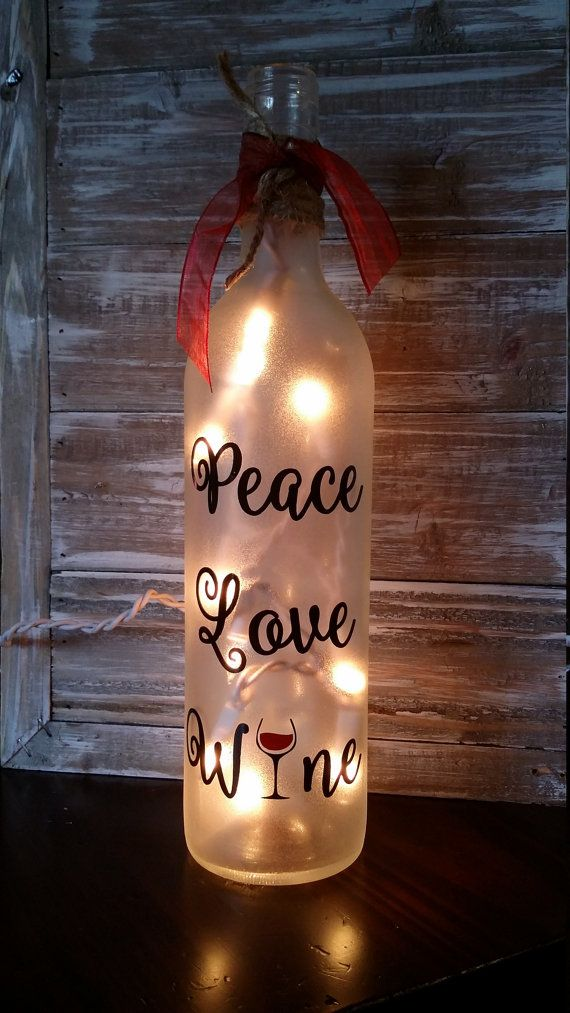 12 frosted wine bottle  A string of white lights run through a hole in the back and plug in  Red ribbon and twine on the top  Light up your counter or the bar with this cute bottle