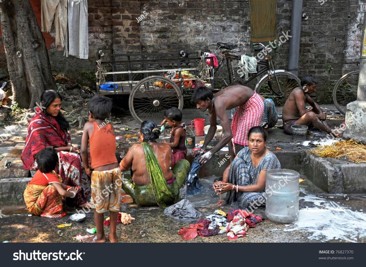 KOLKATA, INDIA - 27 OCTOBER: Indian people wash themselves on a street on October 27, 2009. India contains the largest number of people living below the international poverty line of $1.25/day.