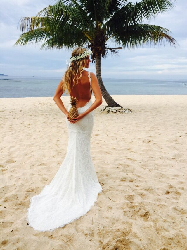 The perfect beachy wedding dress on this beautiful bride with one of her gold pineapples that lined the aisle on the beach. Tavarua Fiji wedding. Perfect destination