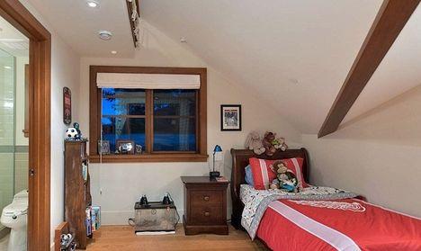 На фотографии мансарда дизайн детской. Маленькая комната отделана белой покраской, чтобы визуально увеличить пространство помещения. В комнате деревянная мебель. Она размещена вдоль стен, чтобы в ц...