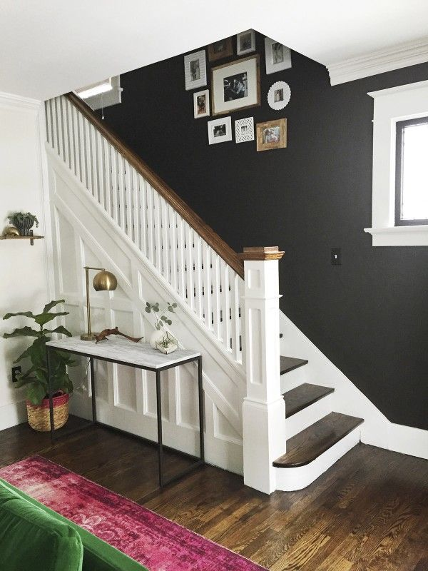 Beautiful entryway and staircase makeover with dark wall and white stairs and…