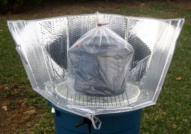 SOLAR COOKER using a reflective windshield shade, black pot, cardboard box and grate.