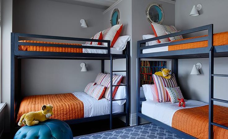 Navy blue and orange boys' bedroom features two sets of navy bunk beds dressed in white and orange bedding placed under porthole windows which looks into a mini library.