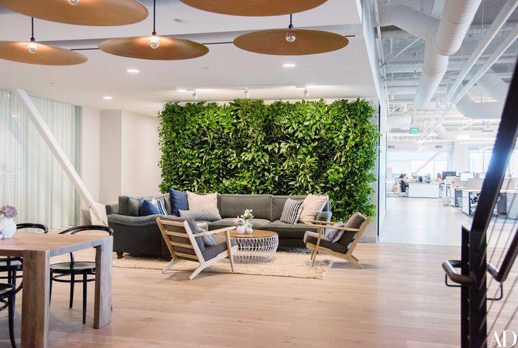 Ambiente no estilo industrial-chic com bastante luz natural, móveis contemporâneos e leves, parede verde e imponentes luminárias redondas e douradas.