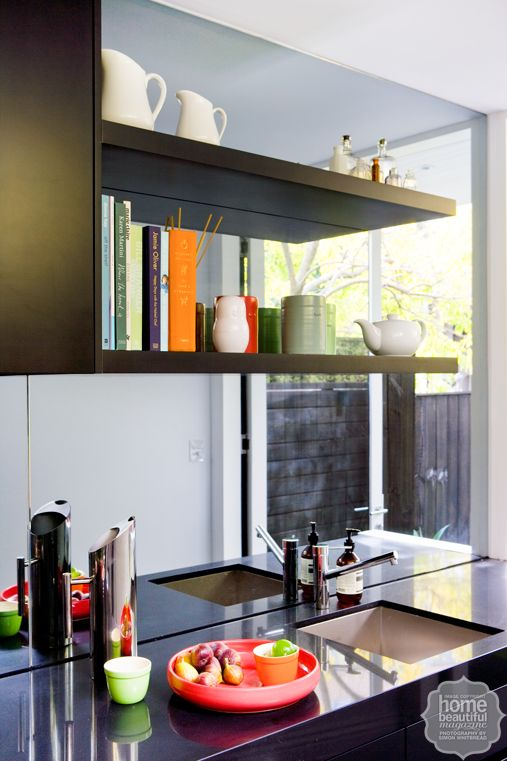 Small wonder: a compact home with big appeal. Mirror splashback and open shelving for cookbooks