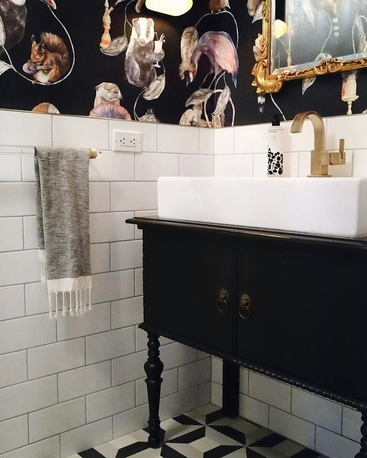 Eclectic bathroom. Graphic black and white tile, bold unique wallpaper, vintage dresser as vanity and white subway tile.