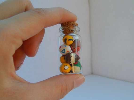 This little glass bottle features Pokemon eggs all stacked in a pile. Everything in this jar is hand sculpted out out Polymer clay, and painted with acrylic paints.  There are 10 Pokemon eggs, and the eggs featured are the eggs that hatch Togepi, Eevee, Cyndaquil, Mudkip, Elekid, Cleffa, Magby, Teddiursa, Vulpix, and Psyduck.  The jar itself is 1 1/2 tall and 3/4 in diameter, and the cork is sealed on with E6000 industrial strength adhesive. Embedded in the cork there is a reinforced eye…