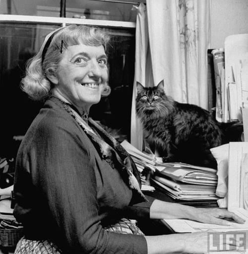 """""""Food writer Clementine Paddleford sitting at desk w. pet cat sitting on her folders close by, prob. in apt."""" New York, 1958, unknown photog..."""