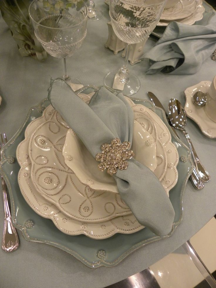Winter table setting: white dishes, pale aqua linens, and a rhinestone brooch as napkin ring.