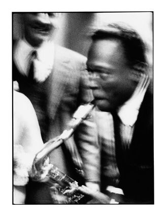 Miles Davis mimics a junkie sax player for  Arrigo Polillo (in the background), Milano 1964