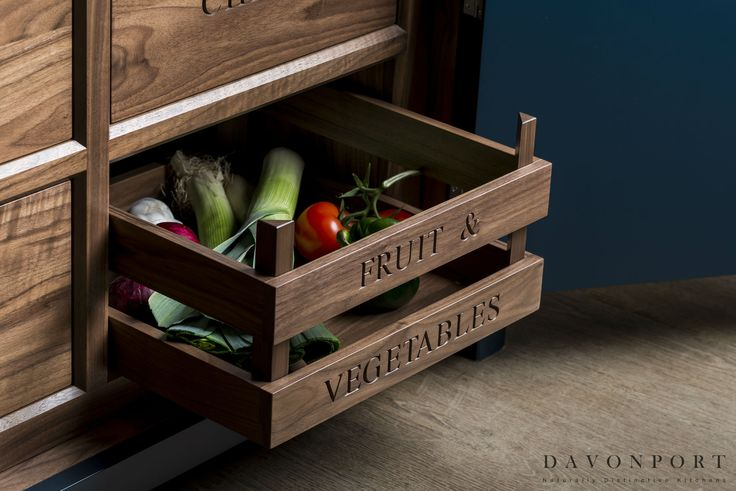 This design takes some of the more traditional aspects of other kitchens and applies them in a contemporary setting. A hand engraved fruit and vegetable drawer in the bottom half of the pantry/gin bar forms a strong feature in an otherwise modern design.