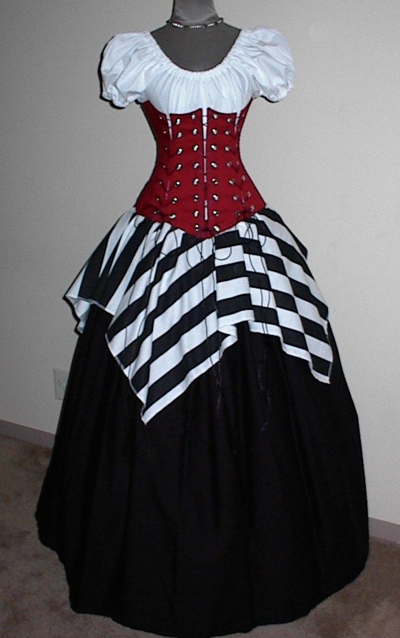 Pirate Wench. The Pirate Wench 4 Piece Set Includes: Puff Sleeve Chemise Top, Long Black Skirt, Jagged Stripe Over Skirt and 4-Tie Under Bust Corset