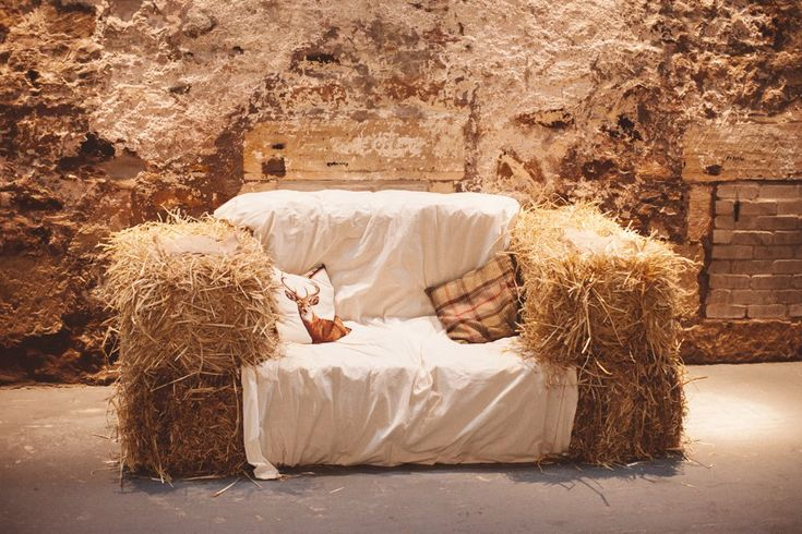 Hay bale sofa seating area - Image by  Christopher Currie Photography - An Essense of Australia wedding dress for a Winter wedding at  Kinkell Byre in Scotland with a pastel rose bouquet photographed by Christopher Currie.