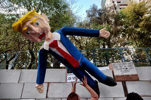 People in Mexico City protest against Donald Trump's inauguration next to a fake wall with a dummy representing him.