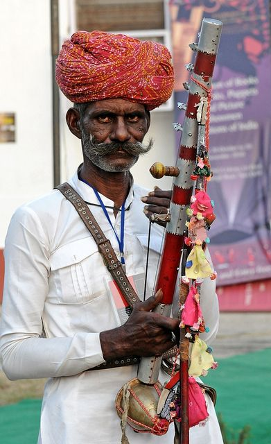 A Rajasthani Folk Singer with his Ravanhatta at the Akhyan festival in Indira Gandhi National Center for the Arts. Ravanhatta is mostly used by Bhopas, who are religious nomadic folk musicians ~it's a primitive string fiddle with one metal and several other strings which may include horse hair and synthetic material. The bow has several bells attached to it and by giving a jerk to the bow, it also provides the rhythm for the lilting music. http://www.youtube.com/watch?v=3U5SJL78TvE