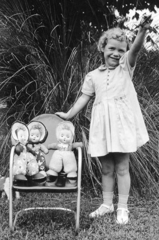 Vintage photo of a cute little girl with triplet cloth dolls circa 1940's - 1950's.