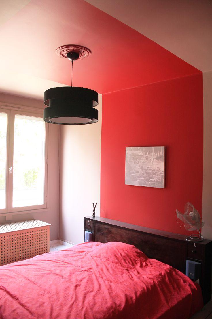 Peinture rouge corail effet baldaquin dans une chambre parentale avec une bande en tête de lit continuant au plafond, constrastée par les murs et plafond couleur taupe chaud.