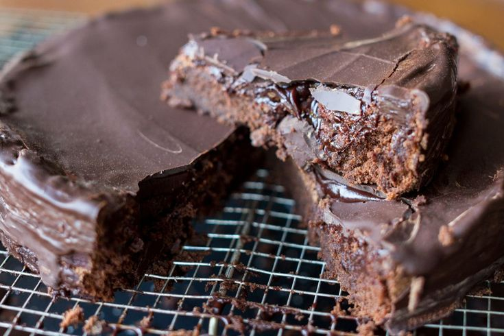 Preheat oven to 170* C (338* F) Fan. Grease a round 23 cm baking pan and dust with cocoa powder. Place a glass or metallic bowl over a pot of simmering water. Add the cho...