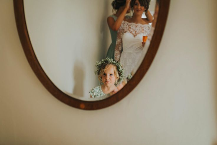 Flower girl and bride share a moment together in the mirror. Photo by Benjamin Stuart Photography #weddingphotography #bride #flowergirl #bridalprep #mirror #reflection #weddingday