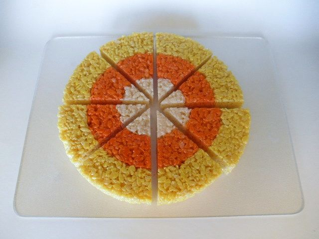 Make candy corn rice crispy treats by adding food coloring to the melted marshmallows and them putting into a round dish.