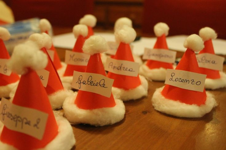 Questi segnaposti natalizi sono dei simpatici cappellini di Babbo Natale fatti con cartoncino rosso e cotone idrofilo, completati da una semplice striscett