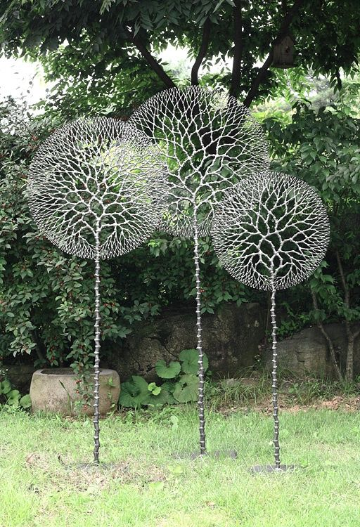metal lawn art - the almost-perfect circles make these art pieces critique systematic conformity - mashing nature into our plastic molds.