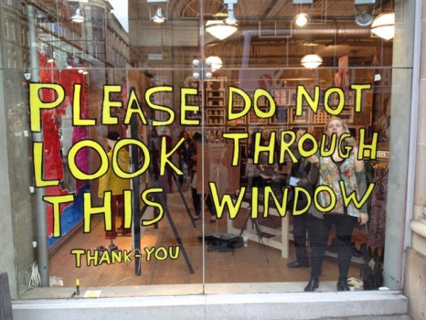 My sign in the window of Urban Outfitters in Glasgow. It's just a joke. You can look through if you want. David Shrigley