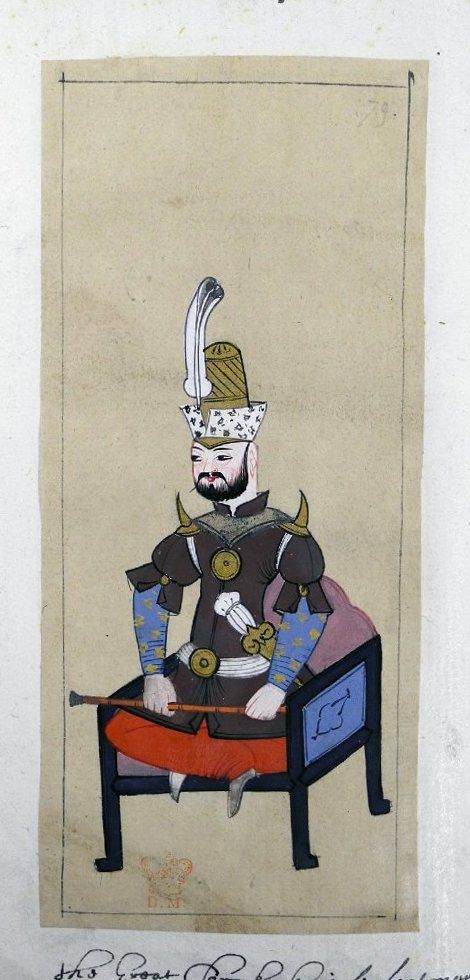 Peyk başı. Superintendent of the peyks. Sitting cross-legged on a white chair, his staff held across his legs. Wearing a short-sleeved brown tunic with sharp spikes as 'epaulettes' on his shoulders. White belt (kemer) with a gold buckle, gold dagger in scabbard. Wearing the külâh-i peyk with plume.