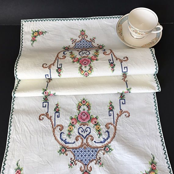 Vintage ivory cotton table runner with beautiful cross stitch embroidery. Nicely embellished piece with cross stitching along the border and a pretty floral design. This heirloom piece would make a nice dresser scarf, also. 40 inches by 16 inches. Laundered and ironed. Excellent vintage condition. Please see photos for details and close ups.  Please see SHOP POLICIES for more info on vintage, shipping, etc...  INTERNATIONAL buyers please take note of possible tariffs, duties, taxes etc in…