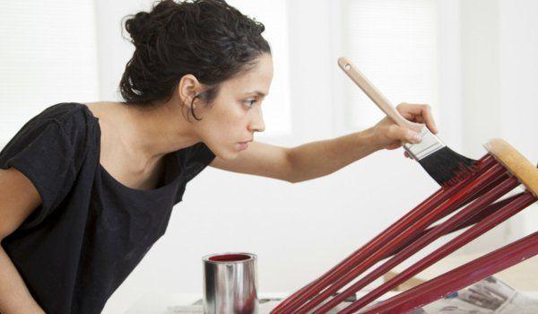 Hispanic woman painting chair