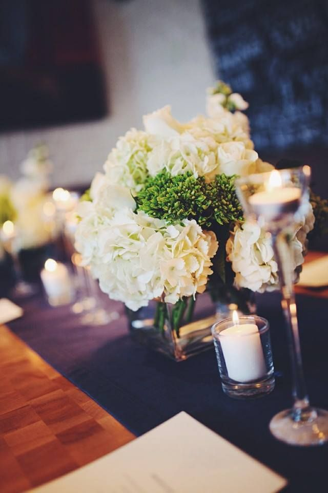Green and white flowers on blue table runner centerpiece for boy's first communion