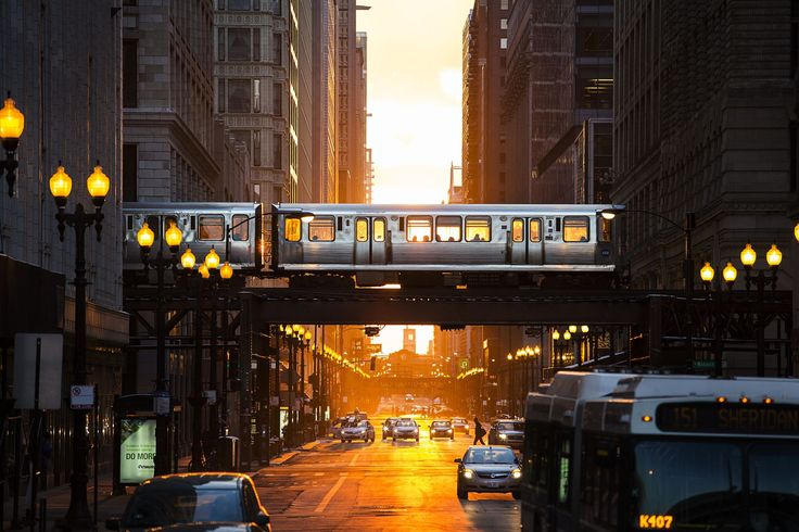 A Chicago L train passes thru the setting sun.
