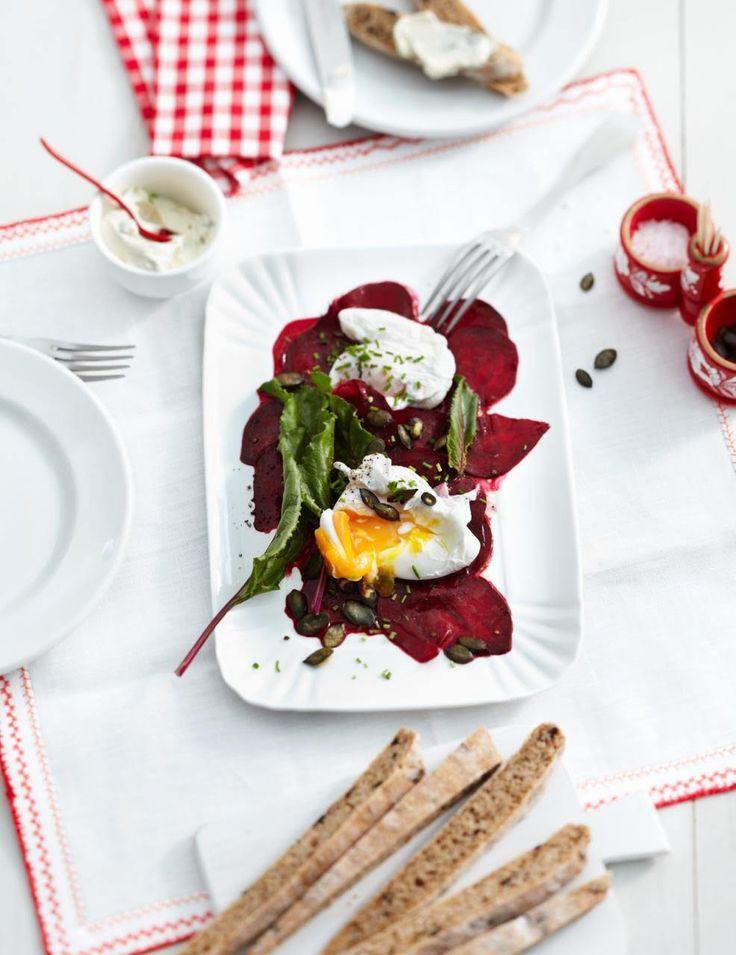 Die Eier werden auf die Rote-Bete-Scheiben gebettet - zusammen mit Crème fraîche, Rote-Bete-Blättern, Kürbiskernen und Schnittlauch.