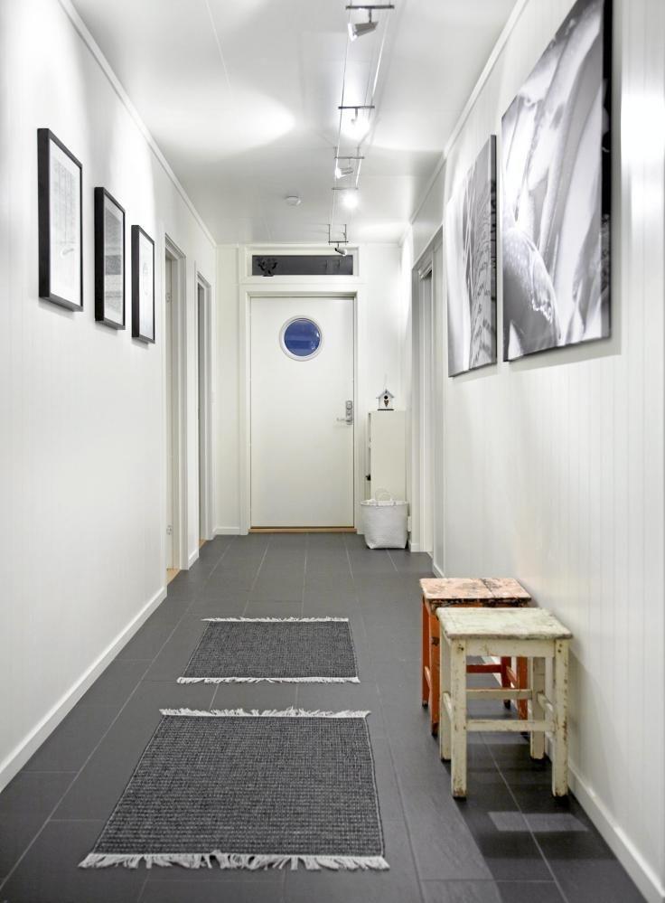 Gjennom huset går det en lang gang. De store fotografiene på veggen er det eieren selv som har tatt.