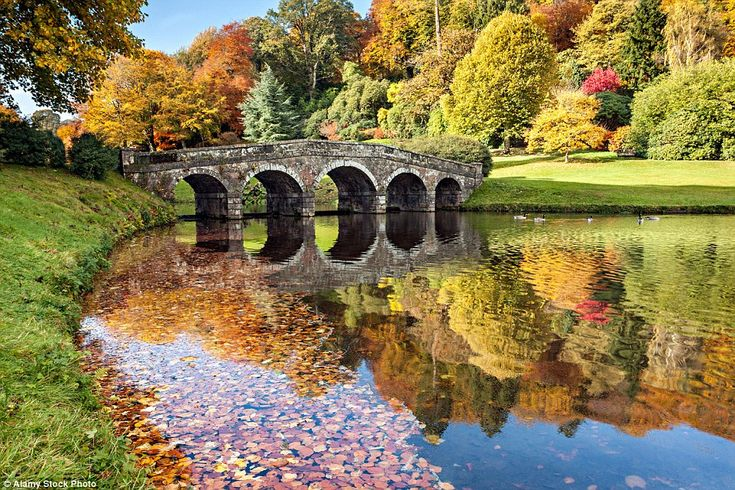 The sight of the Temple of Flora reflected in the lake at Stourhead in Wiltshire on an aut...