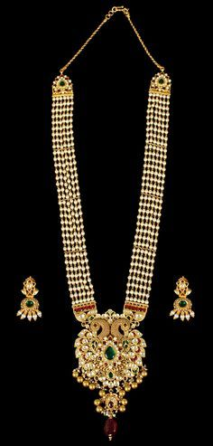 Six rows of translucent pearls strung in gold, exude a luminous and mellow glow. The large peacock pendant is a symphony in resplendent Kundan, red and green stones edged with tiny gold beads