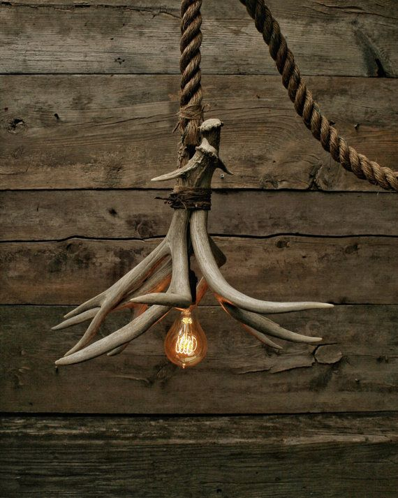 This is the Cabin Lit Chandelier. Ive used 3 Grade A Antler sheds that have been securely bonded and wrapped using Rustic metal twine for aesthetics. Ive ran the electrical cord through the antlers and used a Antique Brass Socket. The best part about the light is that every angle has its own look making this a truly unique piece! The rope connects to our signature rusted steel canopy. Each canopies rust pattern will vary  I can supply enough rope to have hang from any ceiling height, just…