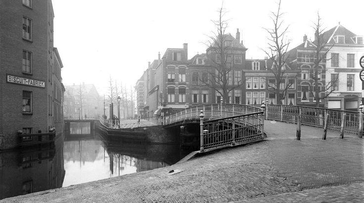 Gezicht op de oude Karnemelksbrug over de Nieuwe Rijn, gezien van de hoek Hartesteeg naar het Gangetje en de Botermarkt. Links de Nutrix biscuitfabriek en de Hogewoerdsbrug met daarachter het Steenschuur (ca. 1937).