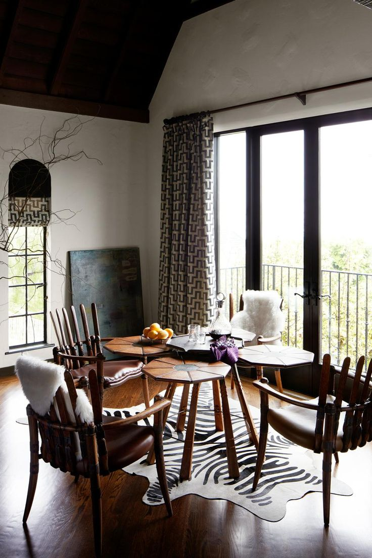 To the side of the seating area, a tiered table holds court with wooden armchairs. A handsome blend of Medieval wood furnishings, an animal-print rug and an artful display of tabletop accessories bring character and rustic charm to the space.
