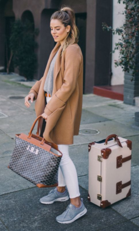 Julia Engel + complements her luggage + oversized tailored camel coat + matching belt + white jeans + Trusty pastel blue trainers + ponytail + perfect for travel days.  Coat: Vince, Sweater: Ralph Lauren, Jeans: Frame, Sneakers: Nike, Bag: Goyard, Luggage: Steamline