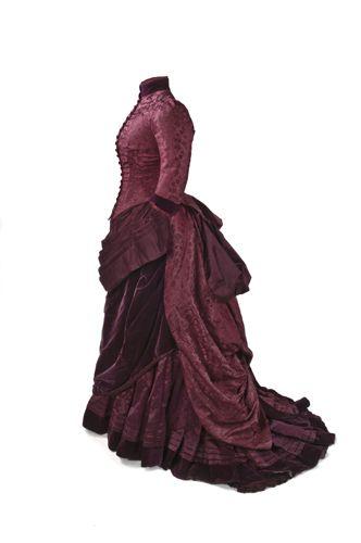 Vestido   1879  Vestido en damasco de seda en color morado, formado por cuerpo y falda. El cuerpo, entallado con doce ballenas, lleva manga de tres cuartos. La falda, en saten, es larga y con cola. En el delantero, un delantal drapeado y una túnica asimétrica. El polisón potencia el volumen de la falda en la parte posterior.  MT000416-17