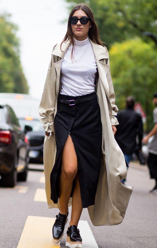 Street style look blusa gola branca, sobretudo bege, saia fenda preta e sapato tratorado.