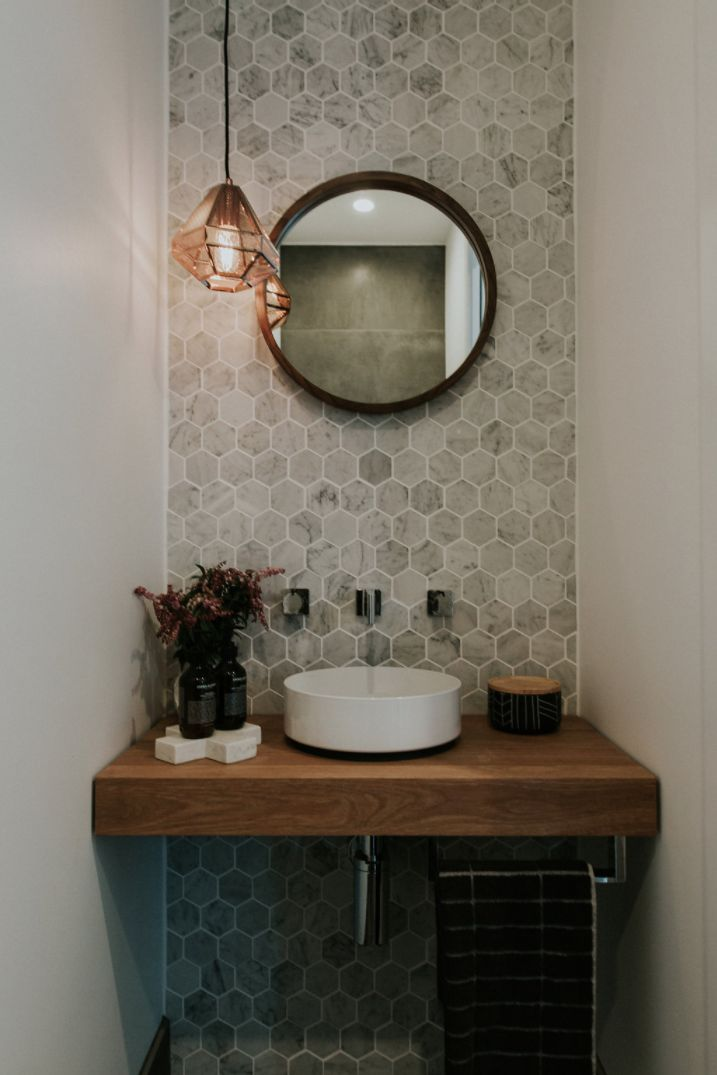 Stunning powder room with marble hexagon wall tiles, round mirror and copper pendant light More