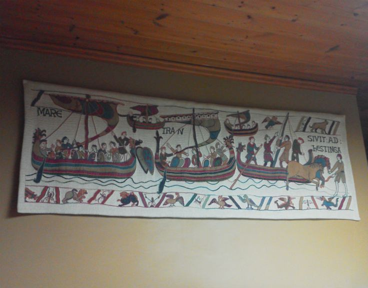 """Bayeux Tapestry ships - hanging in a kitchen. This scene shows five Norman ships from their invasion armada reaching the shore of England. Today woven in France, 27""""x76""""."""