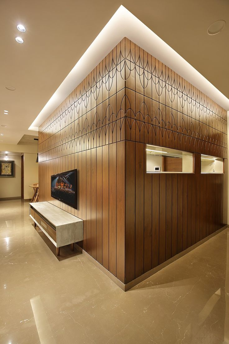 wood art house-the main entrance is designed in teak wood with the customized wooden door handle. the entry wall gives a luxury feel with teak wood