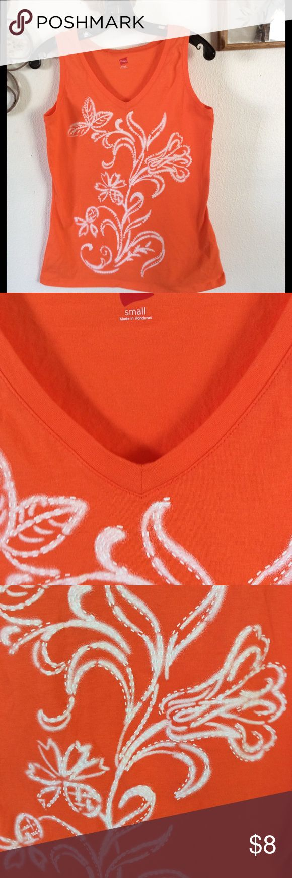 NEW HANES ORANGE  T SHIRT WITH FLOWER OUTLINE NEW NO TAGS HANES ORANGE SLEEVELESS T SHIRT WITH WHITE FLOWER DESIGN ON FRONT. SIZE SMALL. THE OUTLINE OF THE FLOWER IS WHITE PUFFY PAINT LINES.  NEW NEVER WORN. Tops Tank Tops