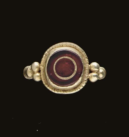 A MEROVINGIAN GOLD AND GARNET FINGER RING Circa 7th Century A.D. The hoop round in section, with spiral wire along each shoulder surmounted by three granules, joined to the underside of the bezel with two volutes, the round two-stepped bezel grooved along the outer edge and set with a circular garnet which is inlaid with a thin ring of gold .31/32 in. (2.4 cm.) wide; ring size 7¾