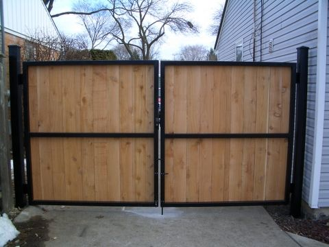 Steel metal gate with wooden fence boards.